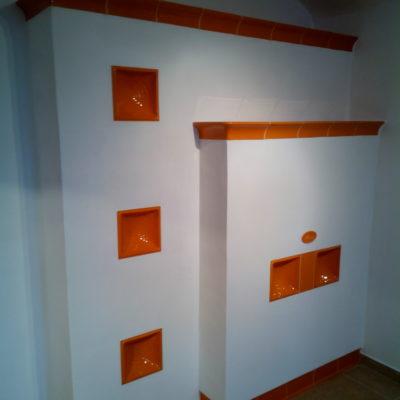 Částečně kachlová a omítaná otopná stěna s bezroštovým topeništěm a přikládáním z druhé místnosti