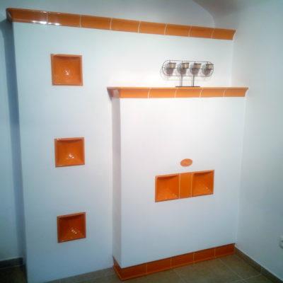 Otopná stěna s bezroštovým topeništěm a přikládáním z druhé místnosti